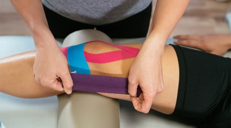 Athletic trainer using colored adhesive to tape up knee