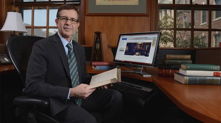 Dr. Christopher Crenner in office, holding book
