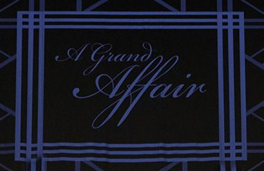"Sign on stage saying ""A Grand Affair"""