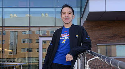 Photo of Chris Melgares in his track suit and KU cross country Tshirt