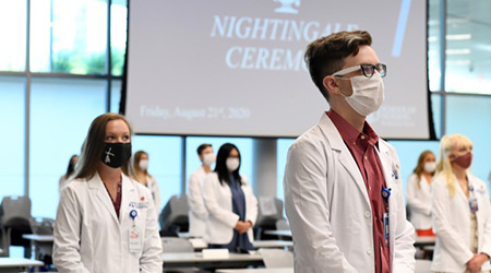 "Nursing students in masks and white coats stand before a screen where ""Nightingale Ceremony"" is shown"