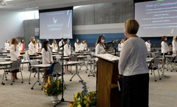 Nursing students in white coats and woman at podium