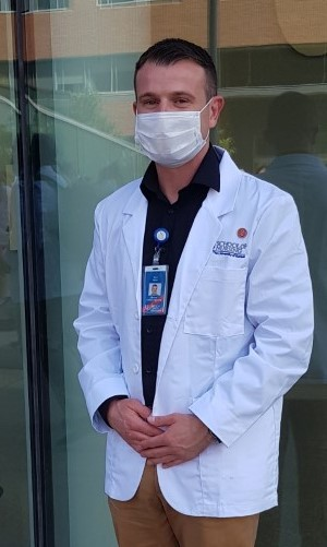 Salter wearing mask and white coat outside HEB