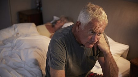 Older man sits awake at edge of bed while woman sleeps