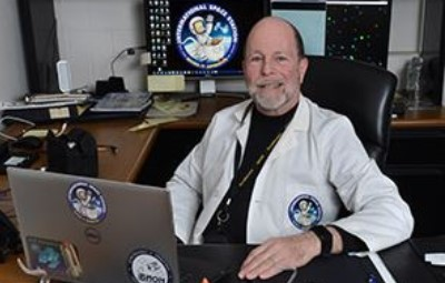 Dr. Tash sits in front of his desk, laptop